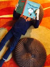 Enfant lisant le livre, allongé par terre sur le dos.